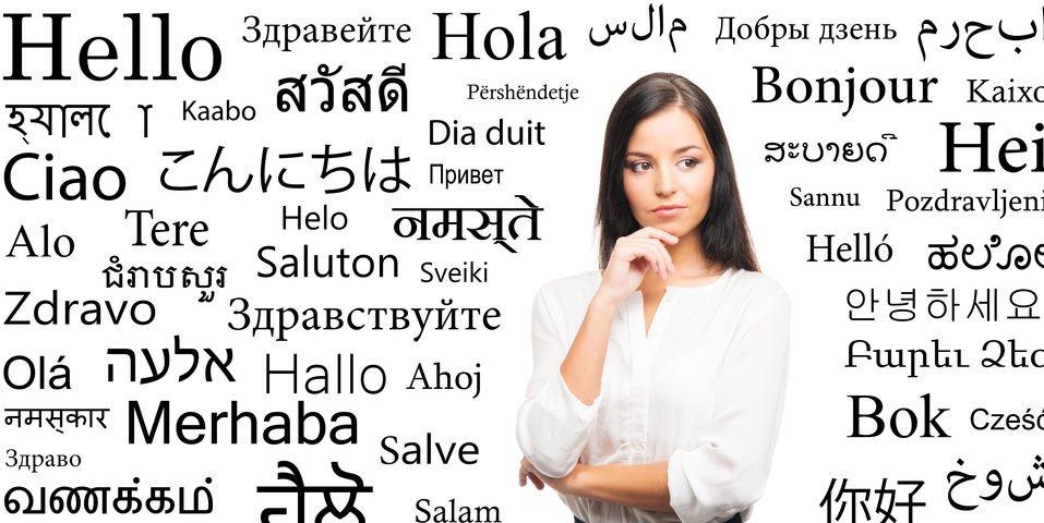 """Frau vor einem Plakat, das """"Hallo"""" in vielen verschiedenen Sprachen zeigt"""