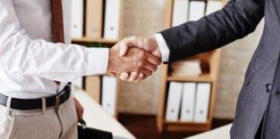 Zwei Männer im Businessoutfit geben sich die Hand