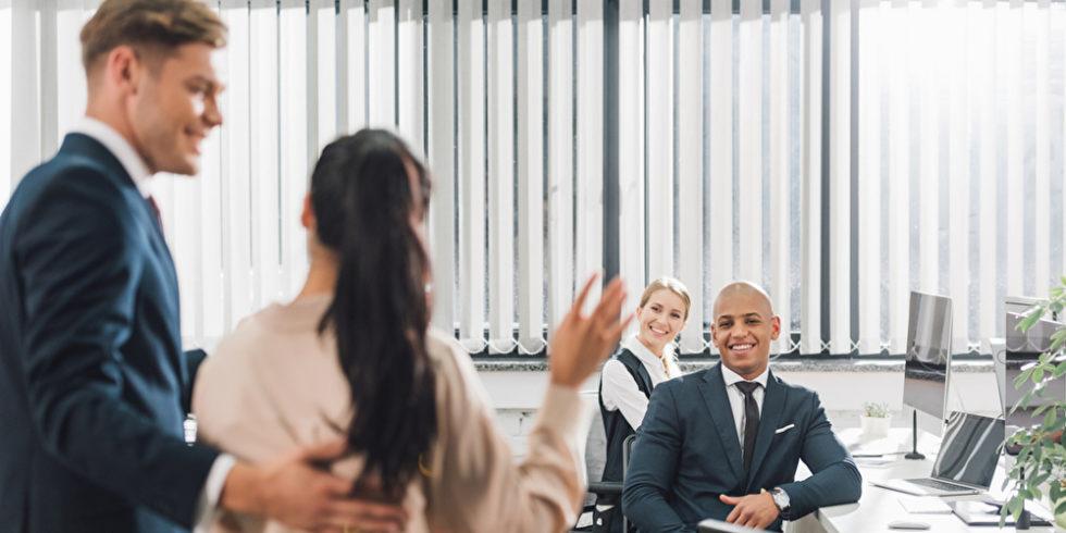 Frau winkt Arbeitskollegen zu