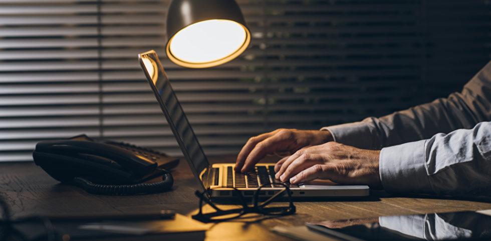 Überstunden: Männerhände an einem Laptop bei heruntegelasenen Jalousien und einer Lampe