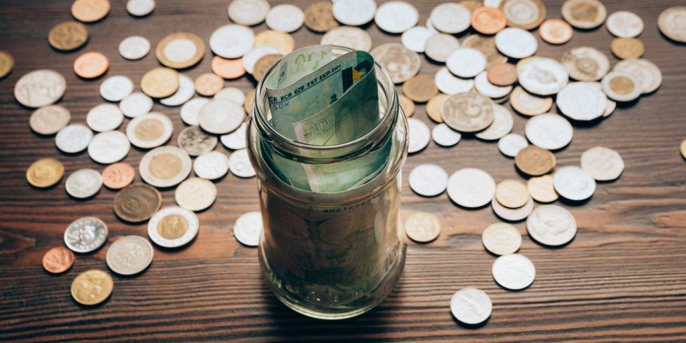 Münzen liegen auf einem Tisch, auf dem außerdem ein Glas mit Geldscheinen steht