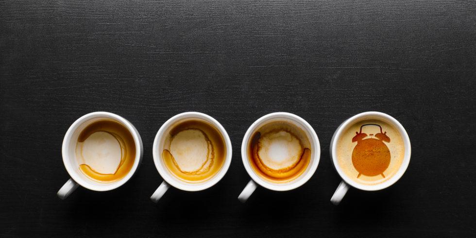 Vier Tassen Kaffee von oben, nur die rechte ist noch voll