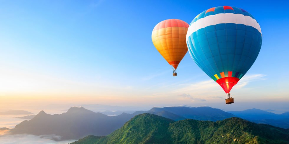 Urlaubsträume: Heißluftballons über Berggipfeln