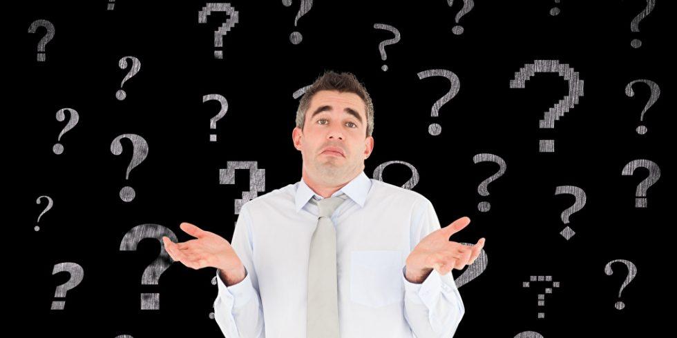 Mann im weißen Hemd und Krawatte wird von Fragezeichen umschwirrt