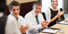 Drei Geschäftsleute sitzen am Tisch und klatschen Beifall