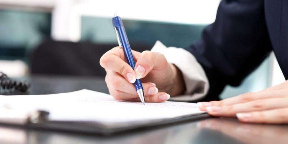 Frauenhände halten einen Kuli und schreiben etwas auf ein Blatt Papier