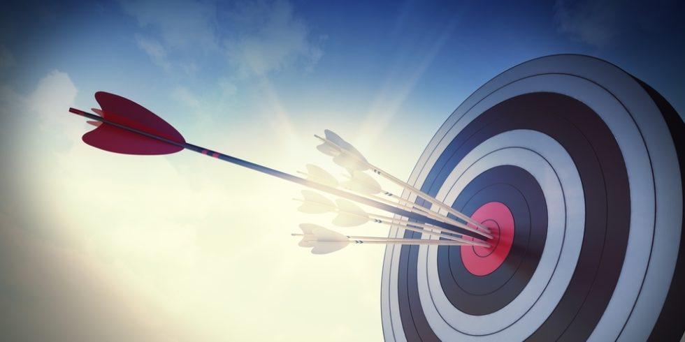 Zielscheibe mit einem großen und vielen kleinen Pfeilen in der Mitte