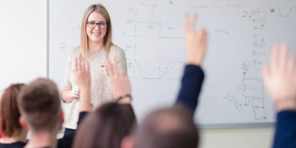 Lehrerin im Klassenraum technische Inhalte an der Tafel