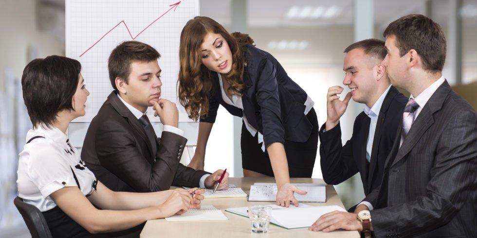 Frau steht vor einem Tisch, an dem Menschen im Businessoutfir sitzen und kritisch schauen