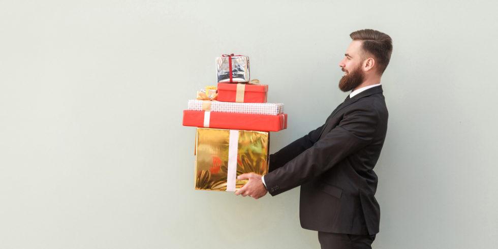 Mann im Anzug hält einen Stapel Geschenke vor sich