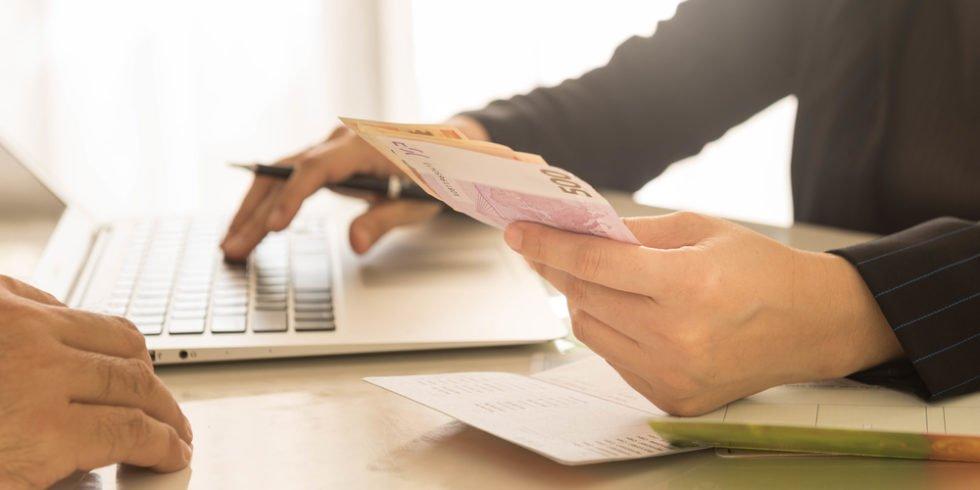 Hand am Rechner hält Geldscheine in der Hand