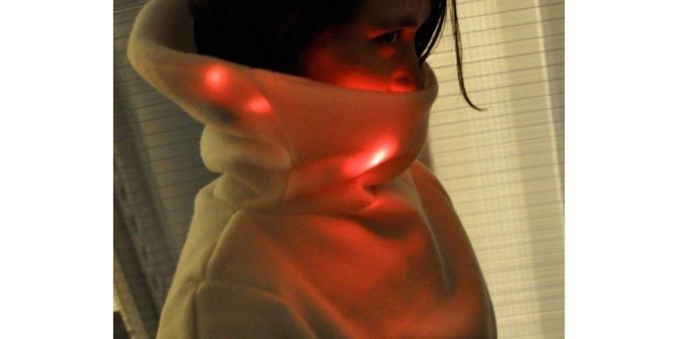 Die junge Frau ist entweder verliebt oder nervös. In beiden Fällen leuchtet der Kragen des Mood Sweaters rot. Foto: Sensoree