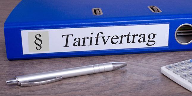 Tarifvertrag steht auf einem Ordnrerücken, der auf einem Tisch liegt