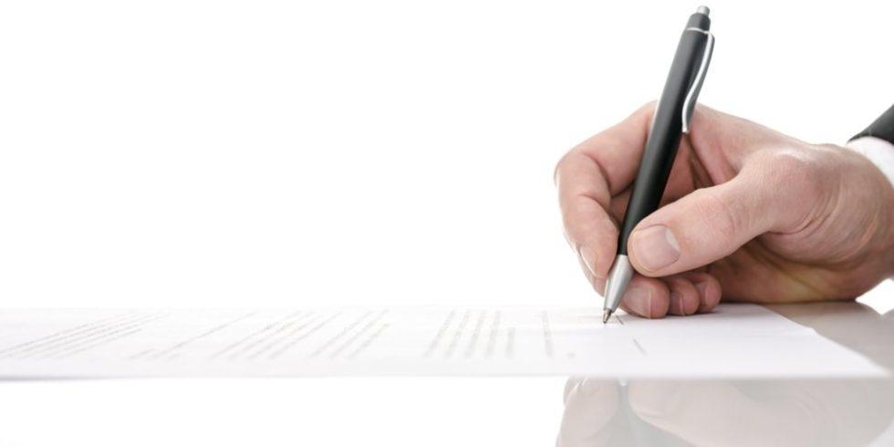 AT-Vertrag: Eine Hand mit Kugelschreiber bei der Unterzeichnung eines Blatt Papiers