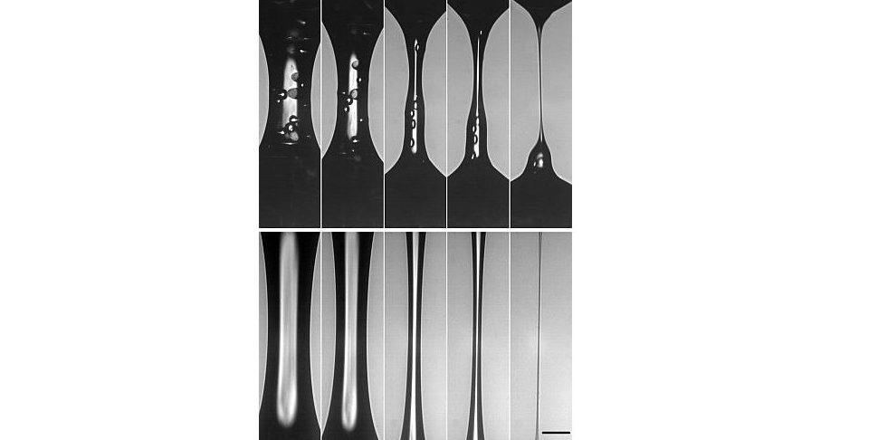 Blick in ein Tropfen-Experiment: Die Forscher konnten erstmals belegen, dass Feststoff-Teilchen in Suspensionen den Tropfvorgang auslösen und beschleunigen.Die fünf Aufnahmen der Hochgeschwindigkeits-Kamera zeigen oben – von links nach rechts – einen Tropfvorgang: Das fadenförmige Gebilde entsteht, wenn die Platten mit der Suspension auseinandergezogen werden. Gut zu erkennen sind die Festkörper-Teilchen, die wie Kügelchen darin schweben. Sie stören die Oberfläche der Flüssigkeit, beulen sie aus und behindern die Strömung der Flüssigkeit innen wie außen. Gleichzeitig beeinflussen sie die Oberflächenkrümmung, der kapillare Druck erhöht sich und der Ablöseprozess wird beschleunigt. Zum Vergleich zeigt das untere Bild das Experiment mit Silikonöl, das keine Festkörper-Teilchen enthält.