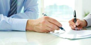 Zwei Männerhände arbeiten gemeinsam an einem Dokument