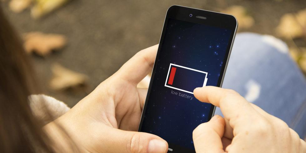 Frau hält Smartphone mit dunklem Bildschirm und leerem Akku-Symbol in der Hand