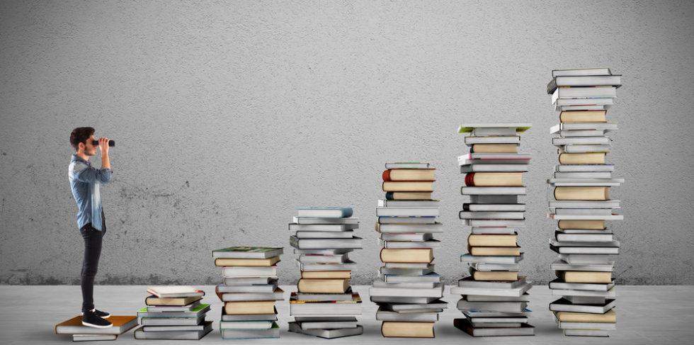 Junger Mann mit Fernglas vor Bücherstapeln