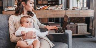 Frau mit Kind auf dem Arm und Laptop neben sich