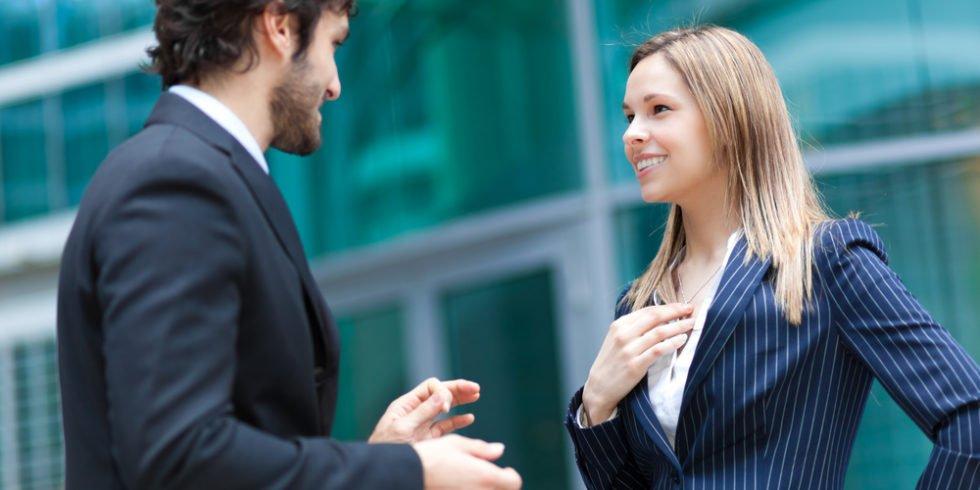 Mann und Frau im Businessoutfit stehen voreinander und sprechen
