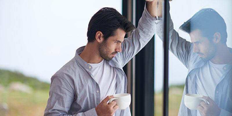 Mann trinkt Kafee am Fenster