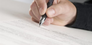 Hand mit Stift markiert einen Text