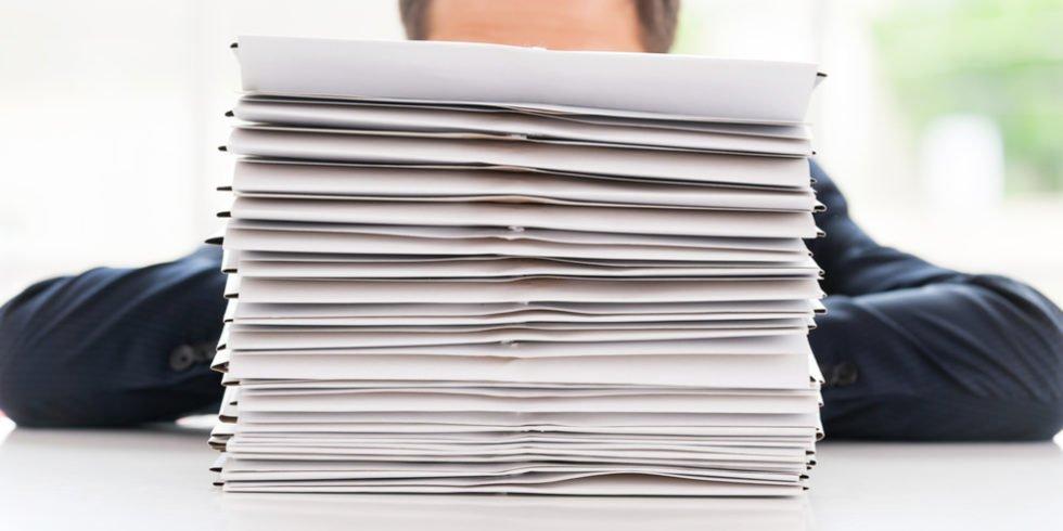 Papierstapel vor Gesicht Mann