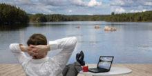 Mann im Anzug sitzt mit Beinen auf dem Tisch an einem See