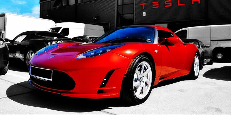 Tesla E-Auto in Rot vor Tesla Gebäude
