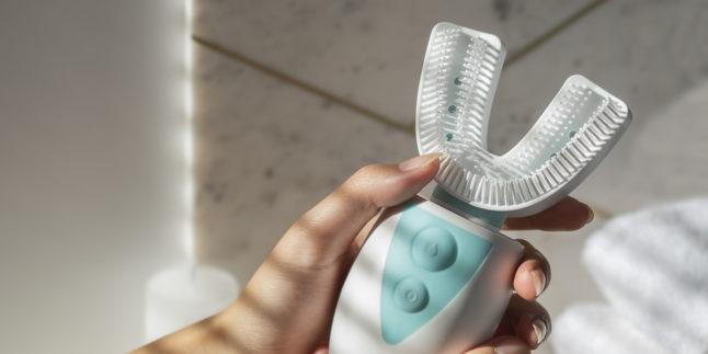 Frauenhände halten die 10-Sekunden-Zahnbürste Amabrush