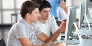 Zwei junge Männer diskutieren vor einem PC-Bildschirm