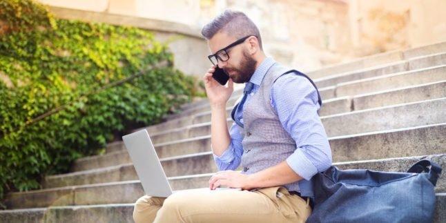 Mann mit Laptop und Smartphone auf einer Treppe