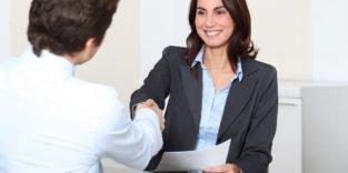 Frau im schwarzen Anzug und hellblauen Hemd gibt Mann mit weißen Hemd die Hand, beide sitzen