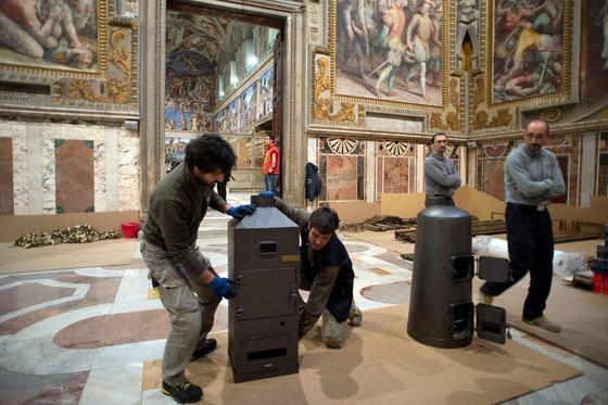 Die Sixtinische Kapelle wird für die Papstwahl hergerichtet. Wichtige Utensilien sind die beiden Öfen – einer für den schwarzen und einer für den weißen Rauch.