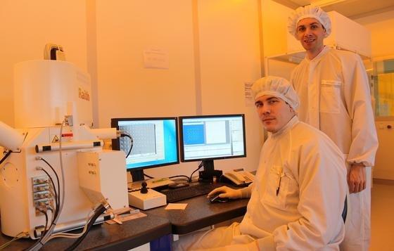 Professor Dr. Thomas Zentgraf (stehend) und Doktorand Holger Mühlenbernd sind maßgeblich an der Entwicklung der Meta-Linse beteiligt. Das Foto zeigt sie im Reinraum des Optoelektronik-Gebäudes der Universität Paderborn.