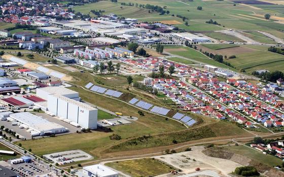Solarkollektoren auf Dächern und Lärmschutzwall sind augenfällige Merkmale des solaren Nahwärmesystems in Crailsheim-Hirtenwiesen. Ein Erdsonden-Wärmespeicher bevorratet solare Wärme für den Winter.