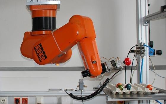 Behutsam setzt der Industrieroboter das rote Ei in eine freie Kuhle auf der Eierpalette.
