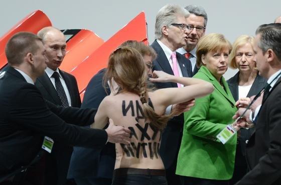 Eine Demonstrantin protestiert auf der Hannover Messe direkt vor dem russischen Präsidenten Wladimir Putin gegen die Menschenrechtsverletzungen in seinem Land. Budeszahlerin Angela Merkel hatte die junge Frau beim Eröffnungsrundgang erst gar nicht bemerkt.