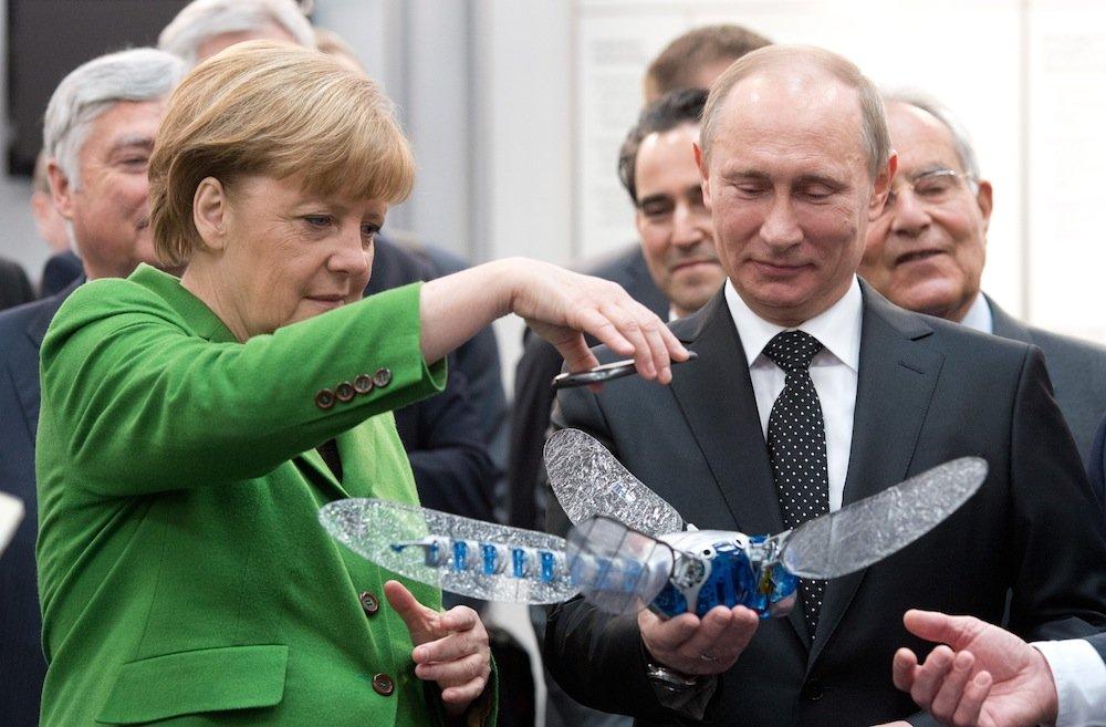 Bundeskanzlerin Angela Merkel und Russlands Staatspräsident Wladimir Putin staunen auf der Hannover Messe am Stand des Unternehmens Festo über eine künstliche Libelle.