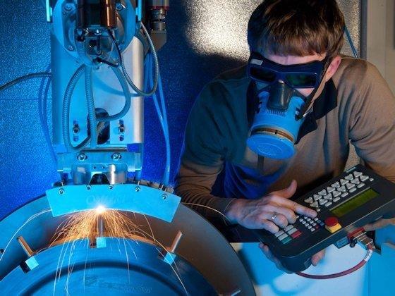 Ressourcenschonende Fertigung und Instandsetzung von Turbinenschaufeln – im Bild der lasergestützte Aufbau von Blisks (Blade Integrated Disks): Auf eine Scheibe werden mithilfe einer Pulverzuführdüse schichtweise Nickel- oder Titanbasislegierungen dort aufgetragen, wo Schaufeln entstehen sollen.