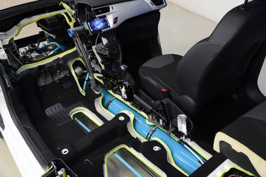 In der blauen Druckluftflasche im Fahrzeugboden speichern die Ingenieure des Autokonzerns PSA Energie, die beim Anfahren genutzt wird. Der Hybridantrieb mit Druckluft soll im Stadtverkehr 45 Prozent Kraftstoff einsparen.