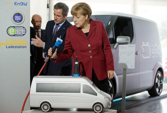 EnBW-Chef Frank Mastiaux (M) erläutert Bundeskanzlerin Angela Merkel während der Internationalen Konferenz zur Elektromobilität in Berlin eine Ladestation am Stand seines Unternehmens.
