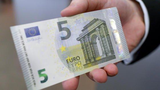 Ein Mitarbeiter der Bundesbank hält am 18. März 2013 in Düsseldorf einen neuen Fünf-Euro-Schein in die Kamera. Der neue Fünfer ist der erste der zweiten Generation der Euro-Scheine seit Einführung des Euro-Bargelds 2002. Er ist seit dem 2. Mai 2013 im Umlauf.