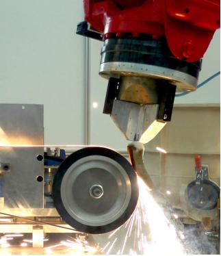 An der Schleifstation bessert der Roboter automatisiert die beschädigten Stellen einer Turbinenschaufel aus.