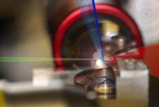<emphasize>Ein Laserpuls (rot) trifft auf Heliumatome (blau), die aus einer Düse mit Überschallgeschwindigkeit entlassen werden. Ein sehr kompakter und kontrollierter Dichteunterschied (dunkelblauer Strahl) entsteht durch eine teilweise Abdeckung der Düse durch eine Rasierklinge. Exakt an diesem Dichteunterschied trifft der Laserpuls auf die Heliumatome, löst dort Elektronen heraus und beschleunigt sie fast bis aus Lichtgeschwindigkeit. Da die Elektronen alle am selben Ort und zudem zeitgleich von den Atomen gelöst werden, haben sie nahezu dieselbe Energie.</emphasize>