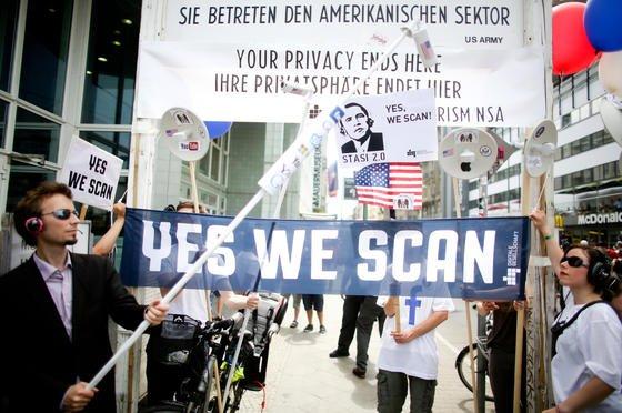 Mit Plakaten demonstrieren Teilnehmer am 18. Juni am Checkpoint Charlie in Berlin gegen das US-amerikanische Internet-Überwachungsprogramm der NSA Prism.