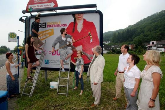 Fünf Marketing-Studierende bekleben die erste Großfläche mit ihrem Gewinnermotiv. 140 weitere Standorte in der Region Koblenz sollen in den kommenden Tagen folgen.