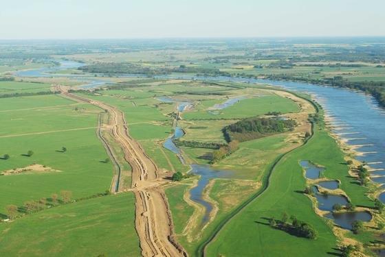 Deichrückverlegung: Die Luftaufnahme zeigtrechts die Elbe und den Altdeich, links die Neudeichbaustelle.