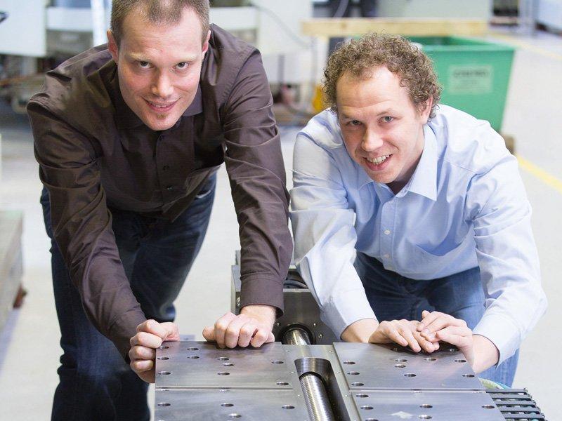 Lars Hülsemeyer (links) und Dominik Dahlmann demonstrieren eine Komponente der effizienten Maschine: Selbst ein stillstehender Schlitten muss normalerweise von einem Antriebsmotor in Position gehalten werden. Hier hält eine Bremse die Achse fest. Unverrückbar!