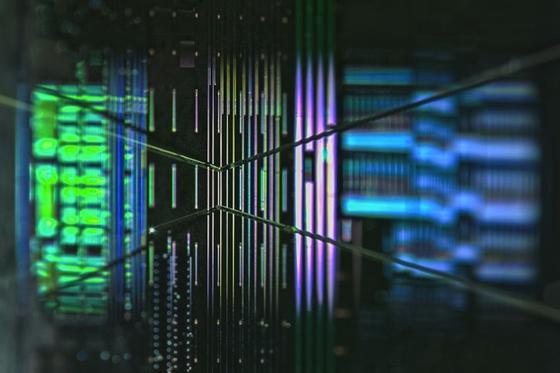 Mikroskop-Bild eines gefertigten Chips in Silizium und auf Gitterstrukturen angebrachter Glasfasern für die Ein- und Auskopplung des Lichts.